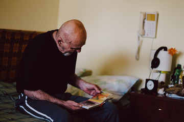 Senior man with a photo album in old peoples home