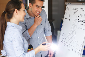 Two office workers making a economy diagram on white board in they office.