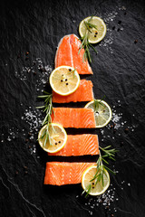 Fresh raw fish fillet cut into portions with lemon slices, salt and pepper on black stone background, top view