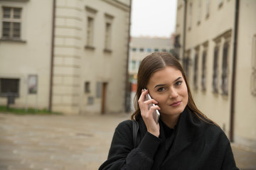 Young girl calling by smartphone on the street