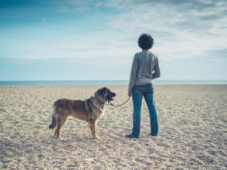 Young man with dog on the beach
