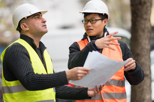 Young Asian apprentice at work on construction site with senior engineer. Outdoors