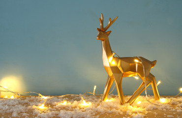 Gold shiny reindeer on snowy wooden table with christmas garland lights.