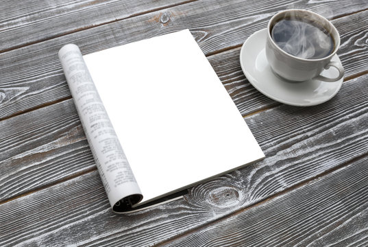 Mock-up magazine on the wooden table. A cup of hot coffee. Blank page or notepad for mockups or simulations.