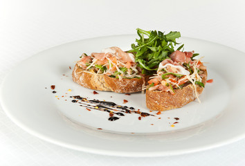 Bruschetta with tomatoes, prociutto ham and rucola