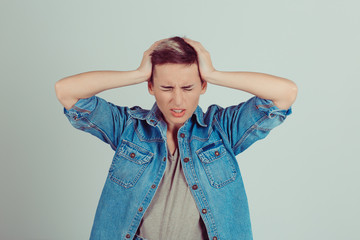 Stressed Pretty brunette getting a headache with hands on head on green grey white background
