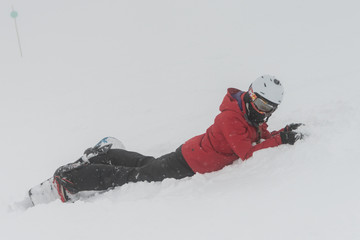 Snowboarder lying on snow , Whistler, British Columbia, Canada