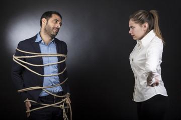 un uomo colpevole in giacca legato con una corda viene guardato da una moglie furiosa - sfondo scuro