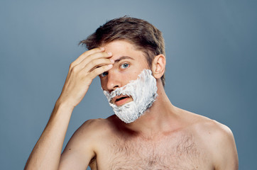 A young guy with a beard on a black background applies a shaving foam
