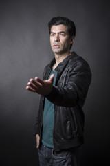 Uomo moro con giacca in pelle e maglietta verde minaccia con la mano aperta pronto a discutere - sfondo scuro