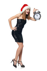 Full length happy Christmas girl in sequined dress and Santa hat with alarm clock counting to midnight