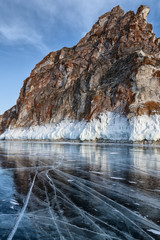 red rock and the transparent ice on the lake Baikal
