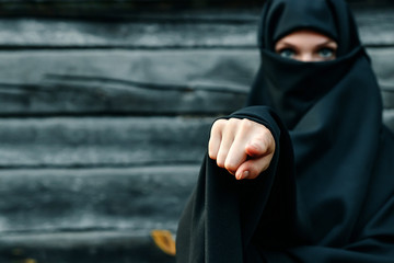 A beautiful, young, Muslim girl in a black veil with a closed face against a gray tree background points her finger at the camera. Copy space.