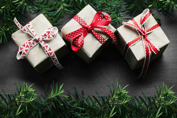 Christmas handmade  presents with red ribbon on wooden background