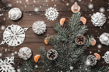 Brown wood background. Fir tree and cones. Sweets. christmas decorations and new year. Slice of mandarins. Xmas and Happy New Year composition. Flat lay, top view