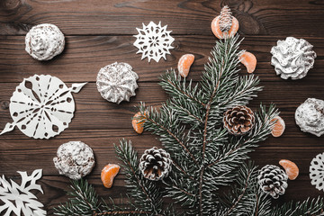Brown wood background. Slice of mandarins. Fir tree and cones. Sweets. Christmas and New Year decorations. Xmas and Happy New Year composition. Flat lay, top view