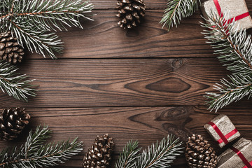 Brown wood background. Fir branches, decorative fir cones. gifts for xmas. Christmas greeting card and new year. Xmas and Happy New Year composition. Flat lay, top view