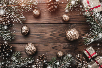 Brown wood background. Fir branches, fir cones and decorative walnuts. gifts for xmas. Christmas greeting card and new year. Snowflakes. Xmas and Happy New Year composition. Flat lay, top view