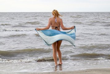 girl in a bikini with a towel in her hands is standing by the sea. A beach walk of the blonde along the shore.