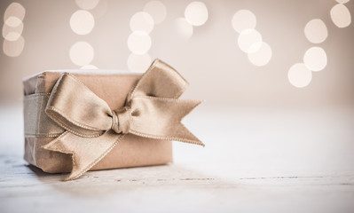 Gift box with satin gold ribbon and blurred background