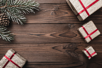 Brown wood background. greeting card. Fir tree, decorative cone. Message space for Christmas and New Year. Gifts for xmas. Xmas and Happy New Year composition. Flat lay, top view