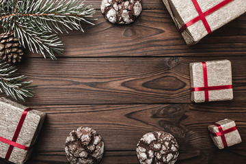 Brown wood background. greeting card. Fir tree, decorative cone. Message space for Christmas and New Year. Gifts for xmas. Sweet biscuits. Xmas and Happy New Year composition. Flat lay, top view