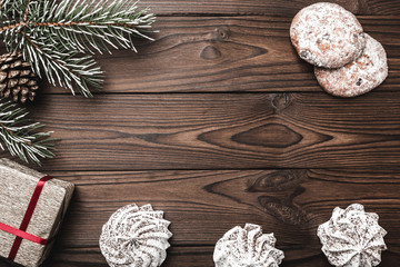 Brown wood background. Fir tree, decorative cone. Sweets. Message space for Christmas and New Year. Gift for holidays. Xmas and Happy New Year composition. Flat lay, top view