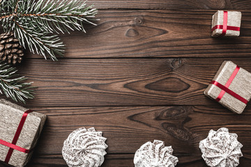 Brown wood background. Fir tree, decorative cone. Marshmallow. Message space for Christmas and New Year. Gift for holidays. Xmas and Happy New Year composition. Flat lay, top view