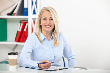 Business woman working in office with documents. Beautiful middle aged woman looking at camera with smile while siting in the office.