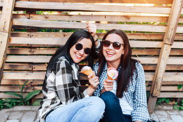 Two pretty brunette girls eating ice cream outdoor