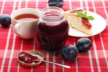 Plum jam in jar with cup of tea and cake on red napkin