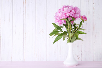 Foto op Canvas Bloemen Bouquet of peony flowers in vase on pink wooden table