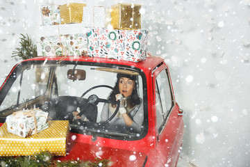 Girl in red car with Christmas gifts
