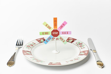 Cutlery and stop sign with banned additives on white background
