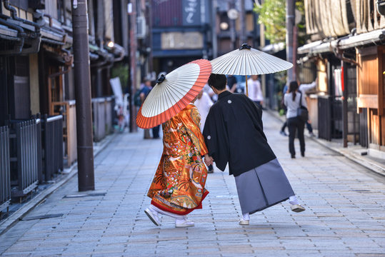 traditional japanese costumes kimono worn by bride and groom with original umbrellas taking photo shots on the marriage day in kyoto japan