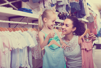 portrait of  woman and girl shopping kids apparel in clothes sto