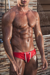 Muscular young sexy wet guy in a speedo in the shower outdoors