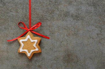 Star-shaped iced biscuit on stone background with red ribbon