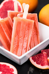 Slate slab with fresh Grapefruit Popsicles (selective focus)