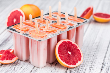 Old wooden table with freshly made Grapefruit Popsicles