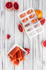 Grapefruit Popsicles (selective focus) on a vintage background
