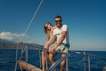 young couple sitting on the bow of the yacht against the sea background, laughing and smiling, the guy is looking at the camera