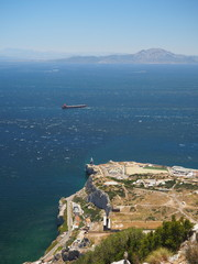 View from the top of the Rock of Gibraltar across the Strait of Gibraltar with passing container ship and Morocco in the distance