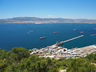 Container and cargo ships around the Rock of Gibraltar with the port of Algeciras, Spain, in the background