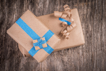 Brown cardboard box with blue and golden bow and ribbon