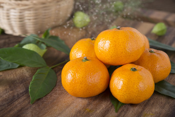 pile of whole fresh Tangerine or Mandarin orange on cutting board