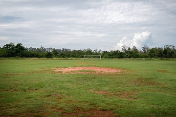 Abandoned football field with nobody and very bad grass, football field with poor ground conditions in the middle of nowhere