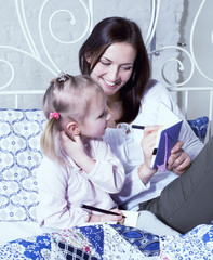 portrait of mother and daughter laying in bed reading and writing, lifestyle people concept