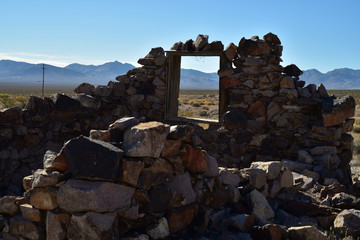 ruins of stone house in ghost town in desert landscape