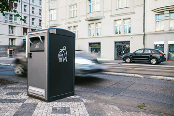 A modern smart trash can on the street in Prague in the Czech Republic. Collection of waste in Europe for subsequent disposal. Eco-friendly waste collection. In the background the car is in motion.